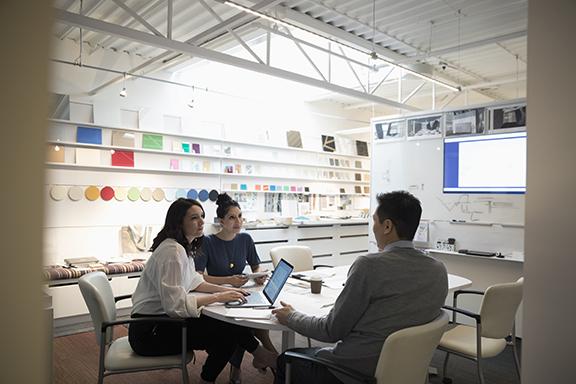 Designers brainstorming, using laptop in creative office
