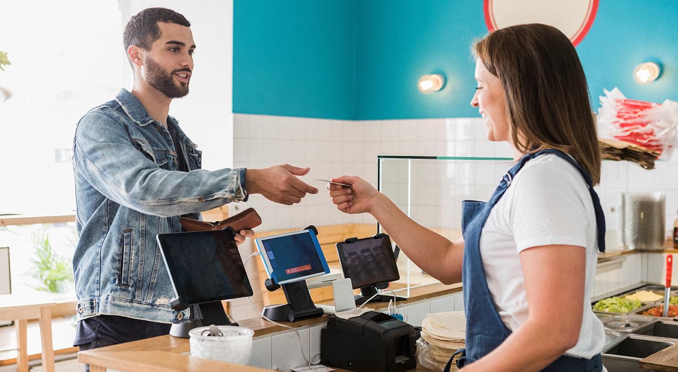 Man paying cashier in cafe