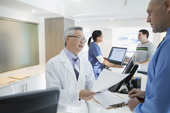 Doctor discussing paperwork with patient in clinic
