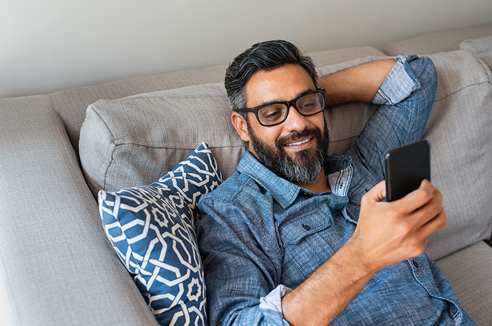 Man relaxing on couch with mobile device