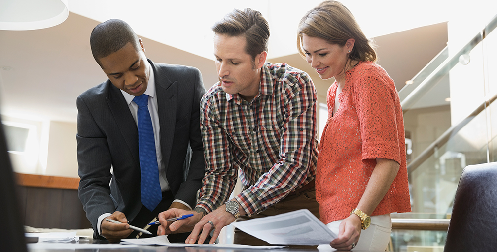 Couple signing documents with realtor