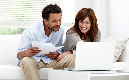 Couple reviewing finances on laptop