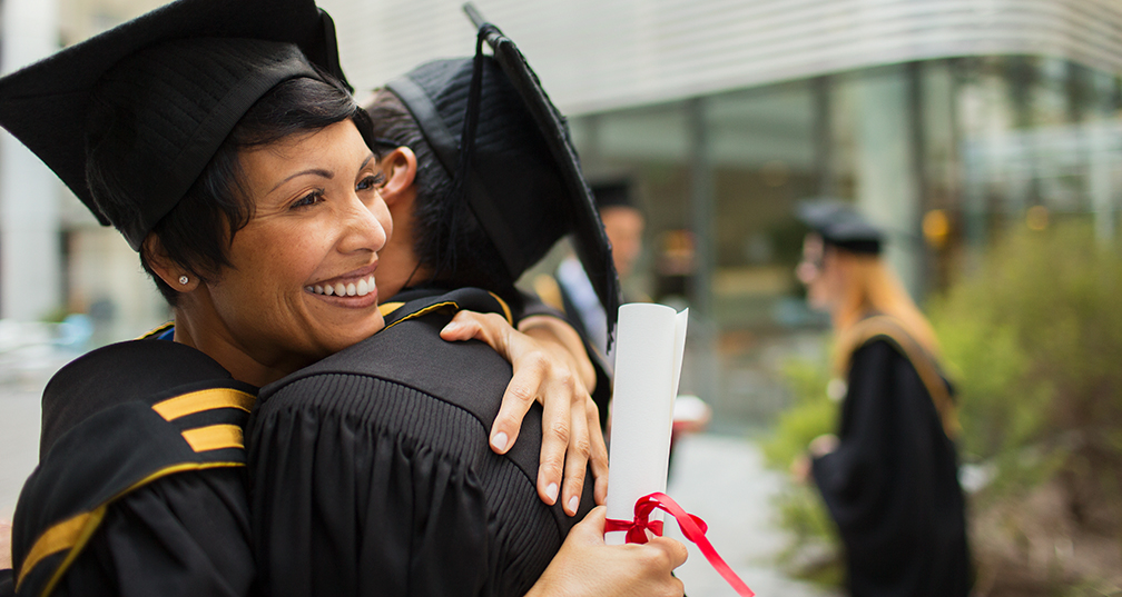 Mature graduate in cap and gown with diploma