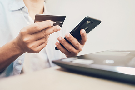 personal holding credit card while using mobile device
