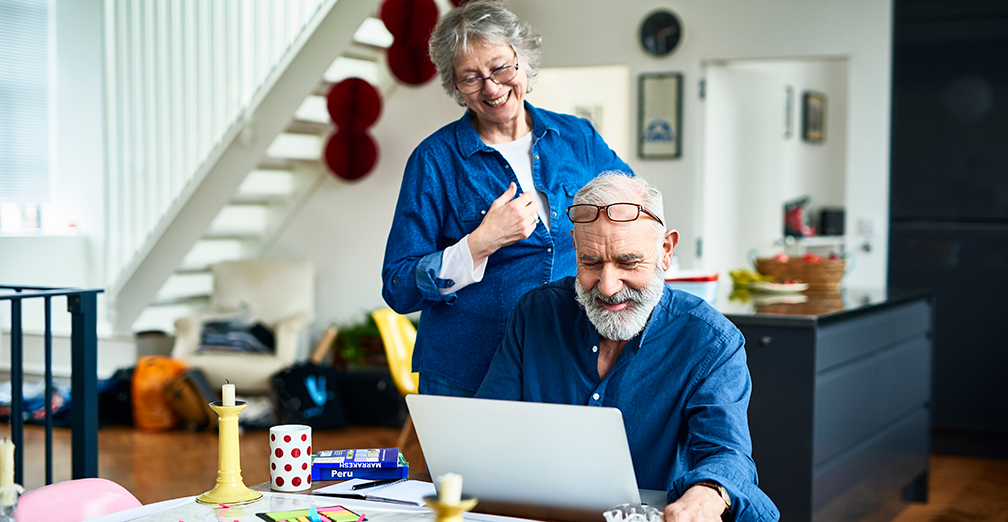 Happy retired couple searching on laptop