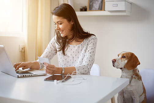 Woman using laptop with dog overlooking