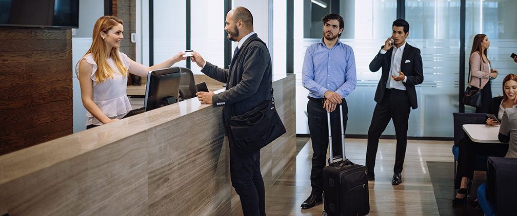 Business travelers using credit card at hotel reception