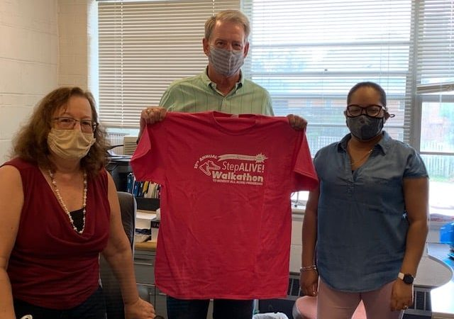 Alexandria ALIVE! drive participants holding T-Shirt